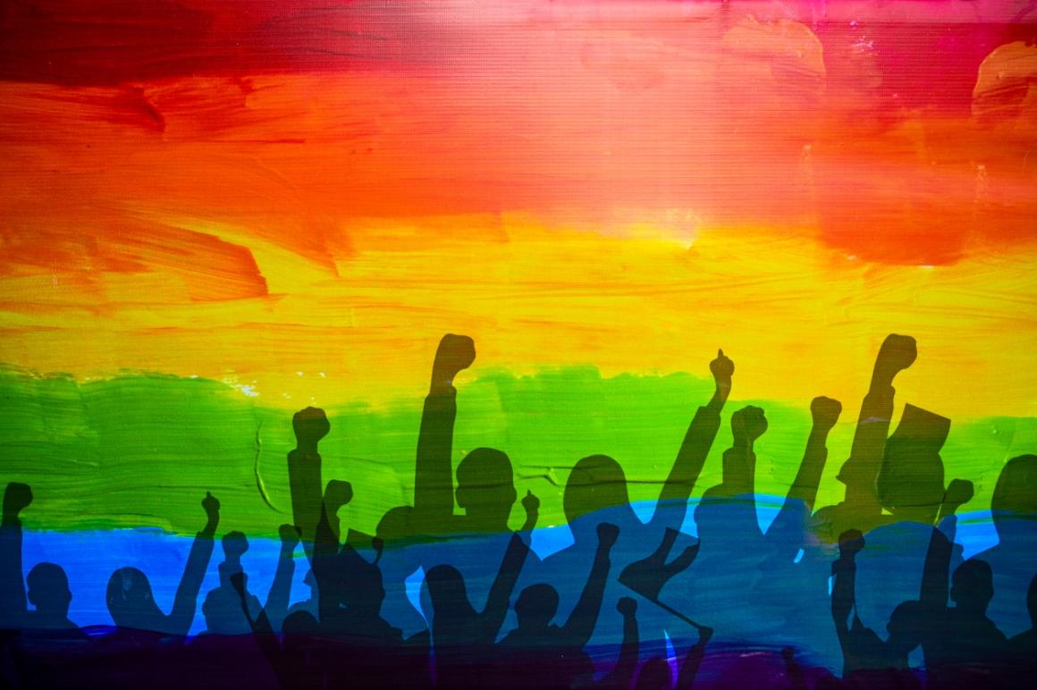 Regenboogmuur met schaduwen van protesterende mensen