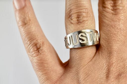 brede zilverkleurige ring met de woorden not just words in gegraveerd